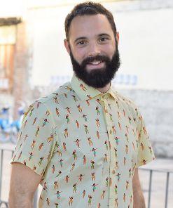 Camisa estampada, de hombre, de manga corta, hecha en algodón orgánico, con estampado de chicas hula sobre fondo vainilla. Tiene cuello italiano, canesú y bajo recto