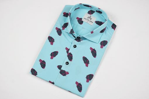 Camisa estampada, de hombre, de manga corta, hecha en algodón orgánico, con estampado de corazones sobre fondo turquesa.