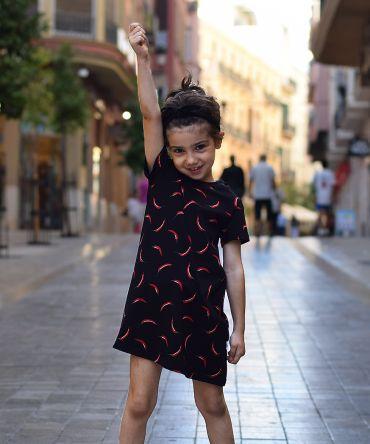 Vestido infantil Chili, hecho en algodón orgánico, de manga corta, con estampado de chilis sobre fondo negro. Hecho en España.