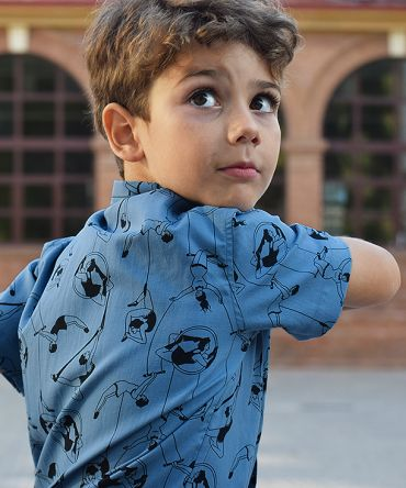 Camisa de niño, de manga corta, con estampado de acróbatas sobre fondo azul. Hecha en algodón orgánico