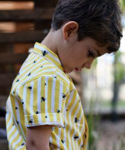 Camisa infantil hecha en algodón orgánico con bonito estampado de moscas y rayas amarillas. Es de manga corta y bajo recto.