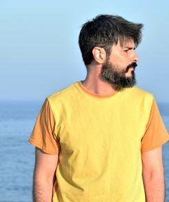 Camiseta color block curry, hecha en punto de algodón orgánico y de manga corta. El delantero es de color curry y las mangas y el trasero color ocre.