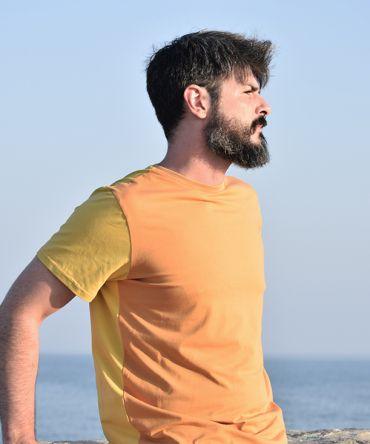 Camiseta color block ocre, hecha en punto de algodón orgánico y de manga corta. El delantero es de color ocre y las mangas y el trasero color curry.