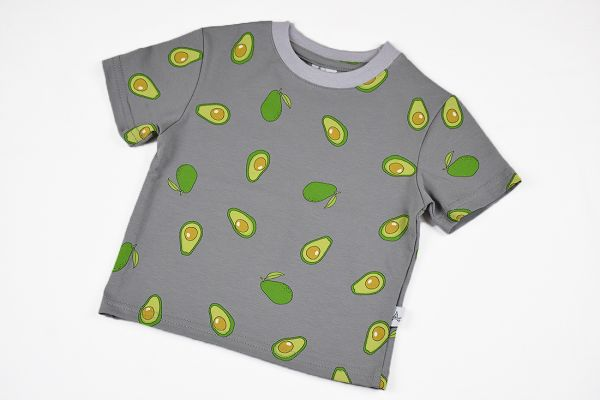 Camiseta infantil Aguacate, de manga corta, hecha en punto de algodón orgánico con estampado de aguacates sobre fondo gris.