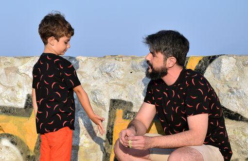 Conjunto de camisetas de adulto y de niño con estampado de chilis sobre fondo negro.