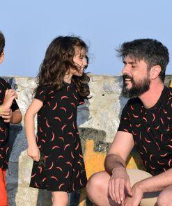 Conjunto de vestido infantil y camisetas de adulto y de niño con estampado de chilis sobre fondo negro.