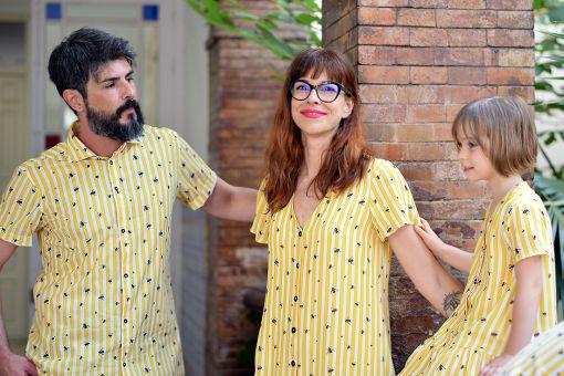 Conjunto de vestidos y camisas infantiles y de adulto con estampado de moscas y rayas amarillas.