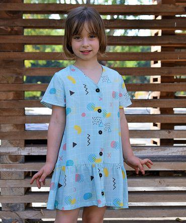 Vestido infantil geométrico, de manga corta, hecho en viscosa, con estampado de cuadrícula y motivos geométricos sobre fondo celeste.