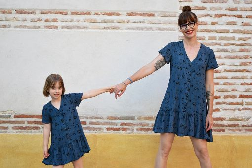 Conjunto de vestidos de mujer y niña con estampado de acróbatas sobre fondo azul.