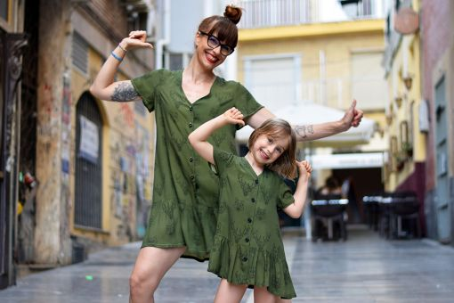 Conjunto de vestidos de mujer y de niña con estampado de animales sobre fondo verde.