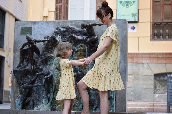 Conjunto de vestidos de mujer y niña con estampado de chicas hula sobre fondo vainilla.