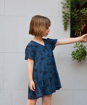 Vestido infantil Acróbatas, hecho en viscosa, de manga corta, con estampado de acróbatas sobre fondo azul. Hecho en España.