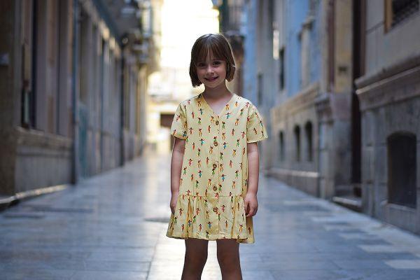 Vestido infantil Hula, hecho en viscosa, de manga corta, con estampado de chicas hula sobre fondo vainilla. Hecho en España de manera sostenible.