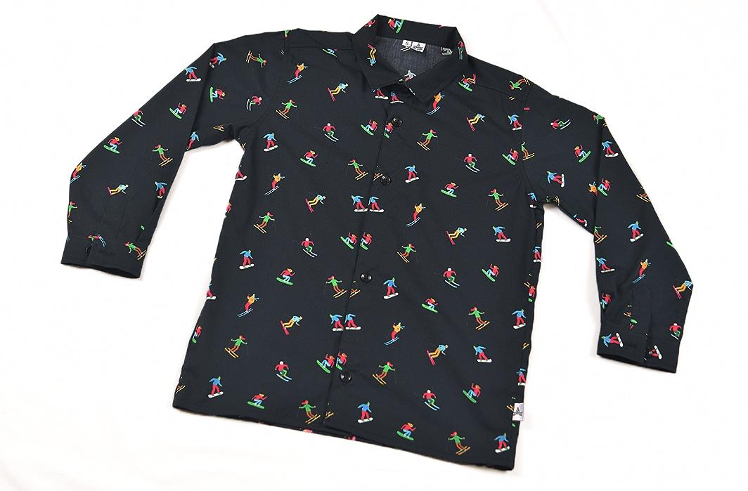 Camisa infantil hecha en algodón orgánico con bonito estampado de esquiadores sobre fondo negro. Es de manga larga y bajo recto.