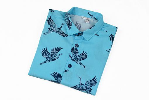 Camisa infantil hecha en algodón orgánico con bonito estampado de grullas sobre fondo turquesa. Es de manga larga y bajo recto.