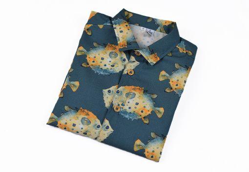 Camisa infantil hecha en algodón orgánico con bonito estampado de peces globo sobre fondo gris. Es de manga larga y bajo recto.
