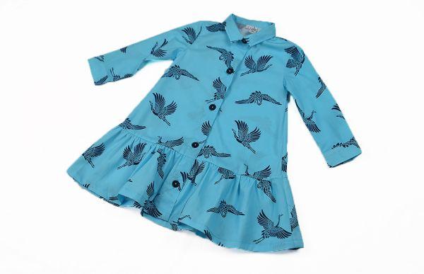 Vestido infantil de manga larga, hecho en algodón orgánico, con bonito estampado de grullas sobre fondo turquesa. Hecho en España.