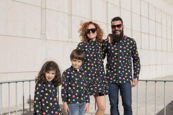 Conjunto de camisas de hombre y de niños y vestidos camiseros de mujer y de niña, de manga larga, de algodón orgánico, con estampado de comecocos sobre fondo negro.