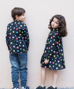 Conjunto de camisa de niño y vestido camisero de niña, de manga larga, hecho en algodón orgánico con bonito estampado de comecocos sobre fondo negro.