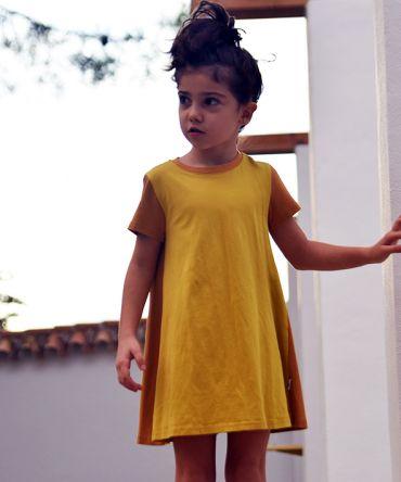 Vestido infantil Curry, hecho en algodón orgánico, de manga corta, combina color curry en el delantero y color ocre en mangas y trasero. Hecho en España.