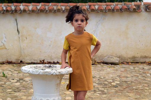 Vestido infantil Ocre, hecho en algodón orgánico, de manga corta, combina color ocre en el delantero y color curry en mangas y trasero. Hecho en España.
