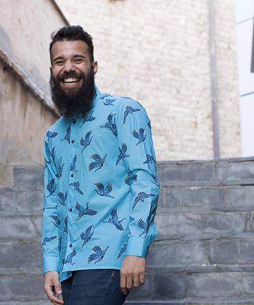 Camisa estampada de hombre, de manga larga, hecha en algodón orgánico, con estampado de grullas sobre fondo turquesa. Es una camisa hecha en España de manera sostenible.
