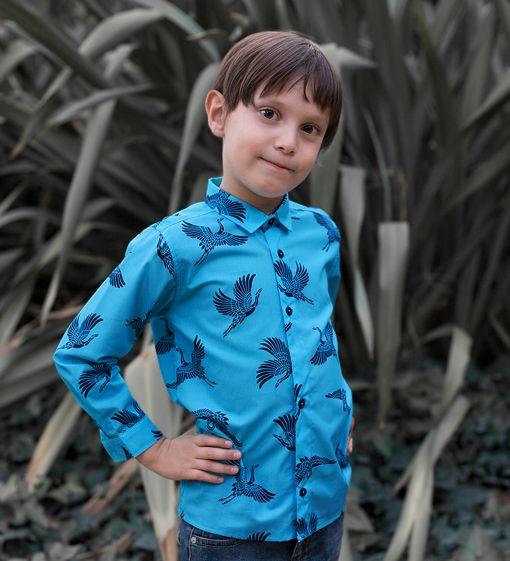 Camisa infantil estampada, de manga larga. Camisa de niño hecha en algodón orgánico con estampado de grullas sobre fondo turquesa. Es una prenda sostenible hecha en España.