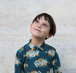 Camisa infantil estampada, hecha en algodón orgánico, de manga larga y con bonito estampado de peces globo sobre fondo gris. Camisa de niño, de bajo recto, sin canesú y cuello de puntas cortas.