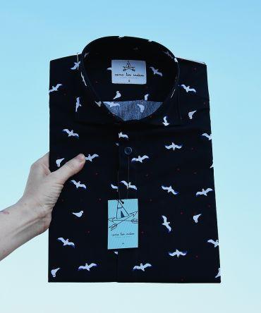 Camisa estampada de hombre, de manga corta, hecha en algodón orgánico, con estampado de gaviotas sobre fondo negro.