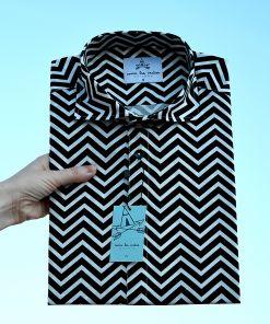 Camisa estampada - Festive Shirt Twin Peaks, hecha en algodón orgánico, con bonito estampado de rayas negras en zig zag sobre fondo blanco. Es de manga corta, tiene bajo recto y cuello tipo italiano.