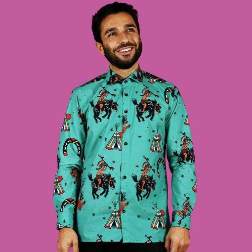 Camisa de hombre estampada con indios y vaqueros sobre fondo turquesa, de manga larga y algodón orgánico. Camisa sostenible hecha en España.