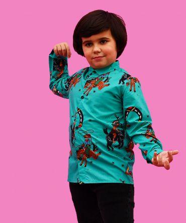 Camisa de niño estampada con indios y vaqueros sobre fondo turquesa. Es de manga larga y está hecha en algodón orgánico, de manera sostenible