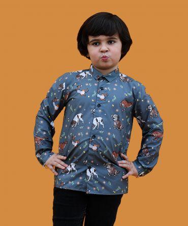 Camisa estampada de niño, hecha en algodón orgánico. Es de manga larga y tiene estampado de perros sobre fondo verde militar.