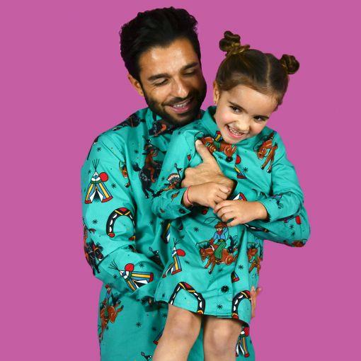 Conjunto de camisa de hombre y vestido camisero de niña, de manga larga y algodón orgánico con estampado de indios y vaqueros sobre fondo turquesa.