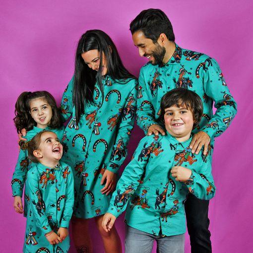 Conjunto de camisas de hombre y niño y vestidos camiseros de mujer y niña con estampado de indios y vaqueros sobre fondo turquesa. Son de manga larga y de algodón orgánico.
