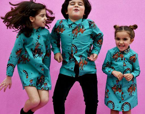 Conjunto de vestidos camiseros de niña y camisa de niño, con estampado de indios y vaqueros sobre fondo turquesa. Prendas para vestir iguales, de manga larga y algodón orgánico. Hecho de manera sostenible en España.