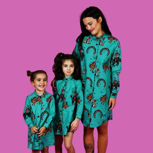 Vestidos camiseros a conjunto de mujer y de niña con estampado de indios y vaqueros sobre fondo turquesa.