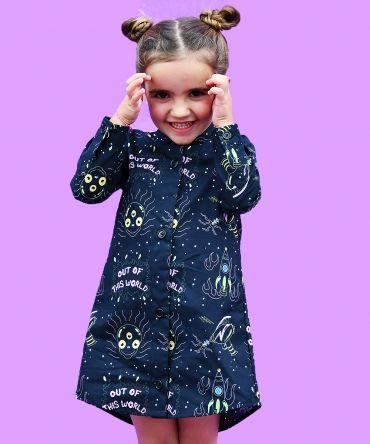 Vestido camisero de niña, de manga larga, hecho en algodón orgánico con estampado de alienígenas y pistolas espaciales sobre fondo negro.
