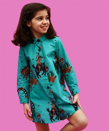 Vestido camisero de niña, de manga larga, hecho en algodón orgánico con estampado de indios y vaqueros sobre fondo turquesa. Hecho en España.