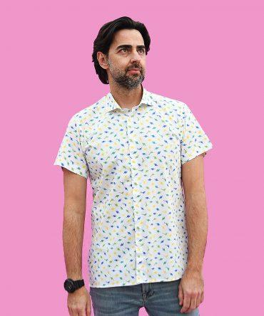 Camisa estampada de hombre, de manga corta, hecha en algodón, con estampado de dinos de colores sobre fondo blanco. Es una camisa hecha en España, de manera sostenible. Tiene bajo recto, canesú y cuello italiano.