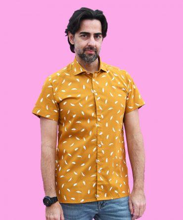 Camisa estampada de hombre, de manga corta, hecha en algodón orgánico, con estampado de plumas sobre fondo mostaza. Hecha en España de manera sostenible.