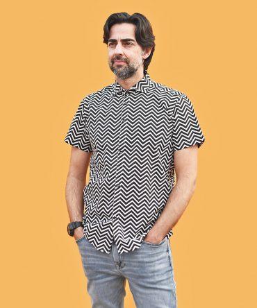 Camisa estampada de hombre, de manga corta, hecha en algodón orgánico, con bonito estampado de rayas negras en zig zag sobre fondo blanco. Tiene bajo recto y cuello tipo italiano.