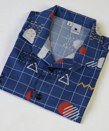Camisa de niño estampado geométrico sobre fondo azul. Es de manga corta y está hecha en algodón orgánico, de manera sostenible.