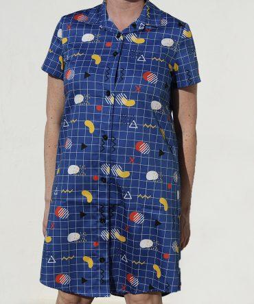 Vestido camisero de mujer, de manga corta, hecho en algodón orgánico con bonito estampado geométrico sobre fondo azul.