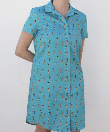 Vestido camisero de mujer, de manga corta, hecho en algodón orgánico con bonito estampado de chicas hula sobre fondo turquesa.
