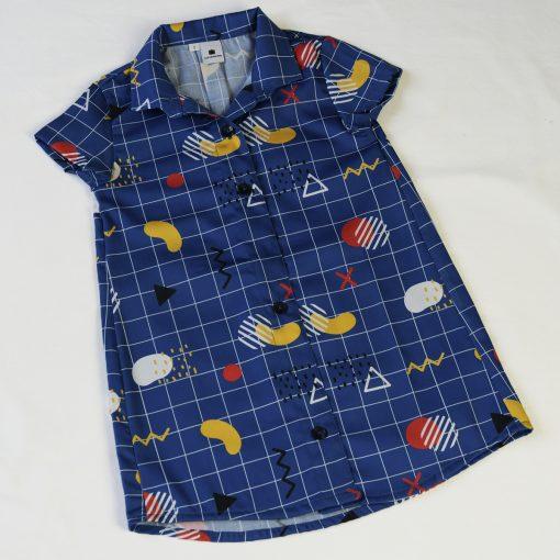 Vestido camisero de niña, de manga corta, hecho en algodón orgánico con estampado geométrico y fondo azul. Hecho en España.