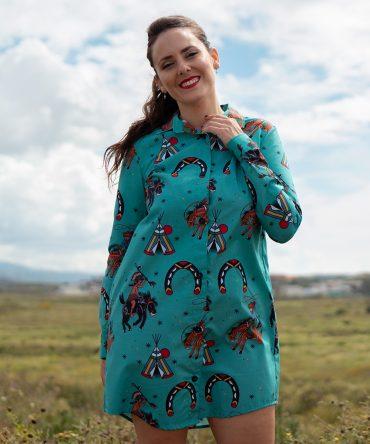 Vestido camisero de mujer, de manga larga, hecho en algodón orgánico con bonito estampado de indios y vaqueros sobre fondo turquesa.
